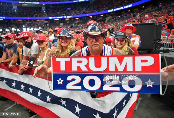 A man holds up a sign as the crowd waits for US President Donald Trump to arrive at a rally at the Amway Center in Orlando Florida to officially...