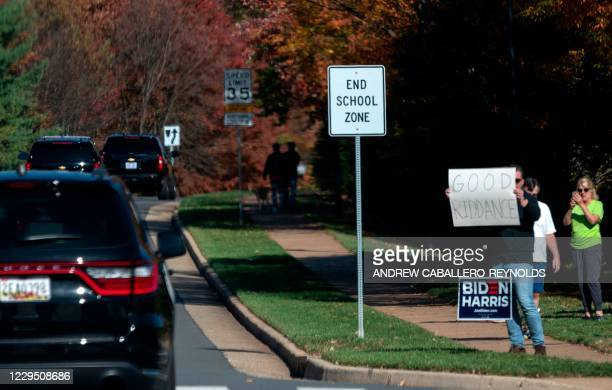 Man holds up a sign as the motorcade with US President Donald Trump drives past in Sterling, Virginia, on November 7, 2020.