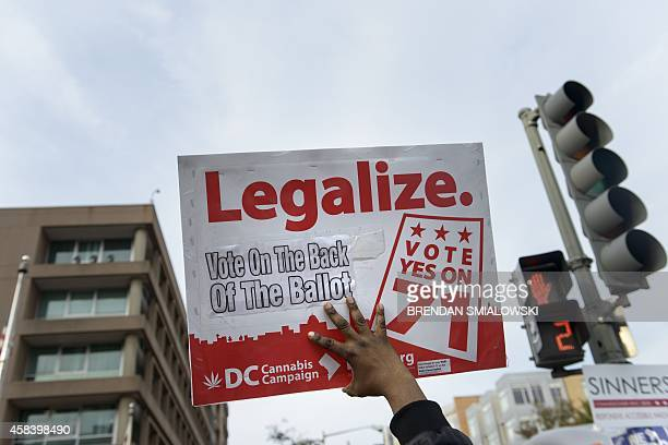 Man holds up a sign for Ballot Initiative, the legalization of marijuana, on November 4, 2014 in Washington, DC. Voters around the United States went...