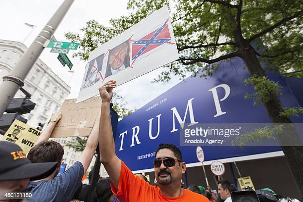 Man holds up a sign in front of the under construction Trump Hotel to protest Donald Trump, candidate for the Republican Presidential ticket, after...