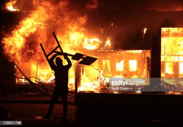 A man holds up a sign near a burning building during protests sparked by the death of George Floyd while in police custody on May 29 2020 in...