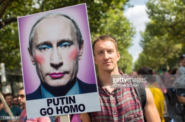 A man holds up a sign reading 'Putin go homo' in Berlin on August 31 2013 during a demonstration 'Enough is enough Stop Homophobia' against the...