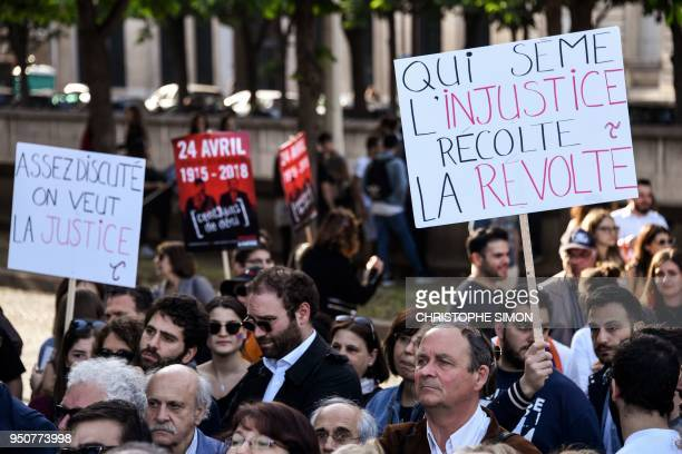 A man holds up a sign that reads in French 'Enough discussion we want justice' and 'He who sows injustice reaps a revolt' as Armenians gather to...