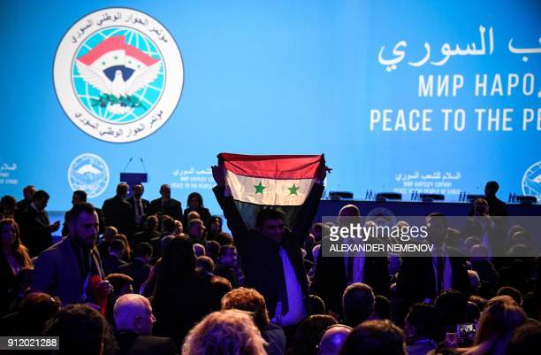 TOPSHOT A man holds up a Syrian flag as attendees wait for the start of a plenary session at the Congress of Syrian National Dialogue in Sochi on...