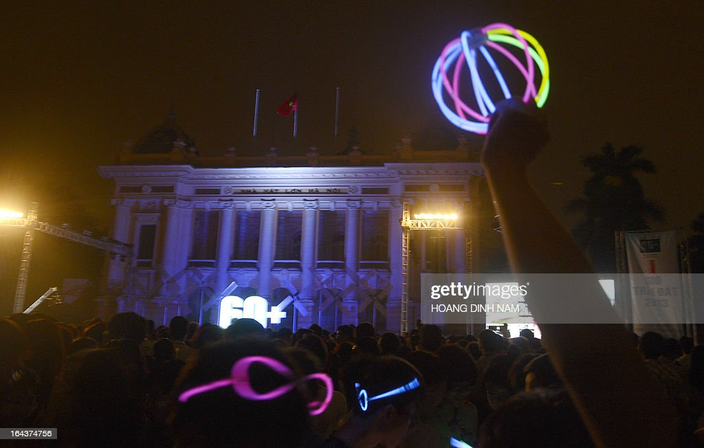 A man holds up a toy in front of Hanoi's Opera House during a black-out moment as part of 'Earth Hour' events in Hanoi on March 23, 2013. Iconic landmarks and skylines were plunged into darkness on Saturday as the 'Earth Hour' switch-off of lights around the world got under way to raise awareness of climate change. AFP PHOTO/HOANG DINH Nam