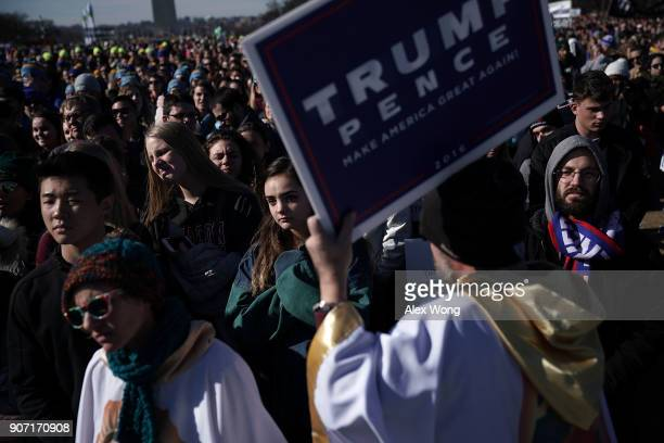 A man holds up a TrumpPence campaign sign as prolife activists participate in a rally at the National Mall prior to the 2018 March for Life January...