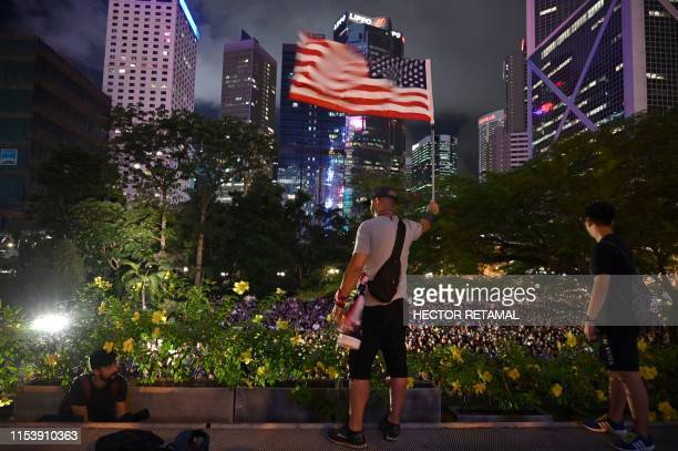 TOPSHOT A man holds up a US flag in front of a rally organised by Hong Kong mothers in support of extradition law protesters in Hong Kong on July 5...
