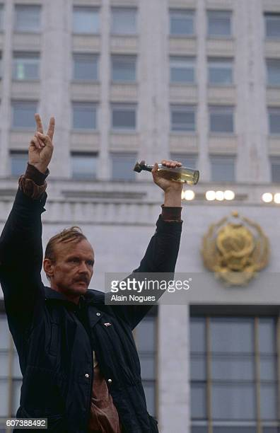 A man holds up a victory sign and a bottle at a demonstration outside the Russian White House during a 1991 coup attempt in Moscow The State...
