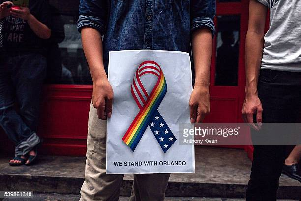 A man holds up a 'we stand together with Orlando' poster as people take part in a candlelight vigil for the victims of a shooting in a gay nightclub...