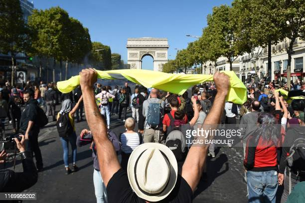 """Man holds up a yellow vest in front of the Arc de Triomphe on the Champs Elysees avenue during an anti-government demonstration called by the """"yellow..."""