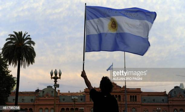A man holds up an Argentinian flag during a demo at Mayo square in Buenos Aires on January 19 against the death of Argentine public prosecutor...
