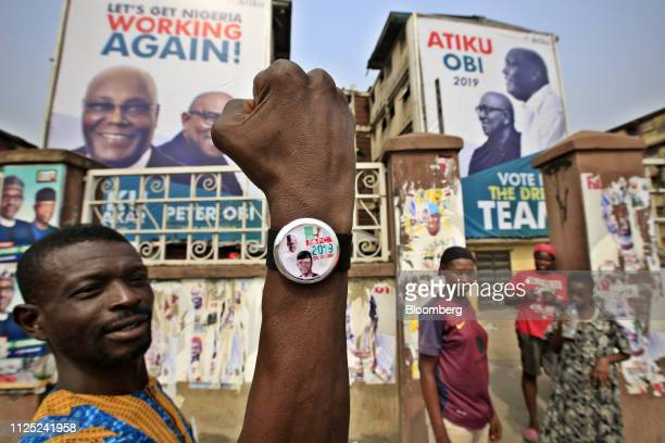 A man holds up an election themed wristwatch near campaign posters of Muhammadu Buhari Nigeria's president and candidate of the ruling All...