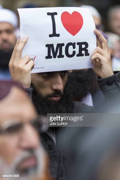 A man holds up an I love Manchester sign as multifaith leaders lay floral tributes in St Ann's square for the victims of the Manchester bombing in...