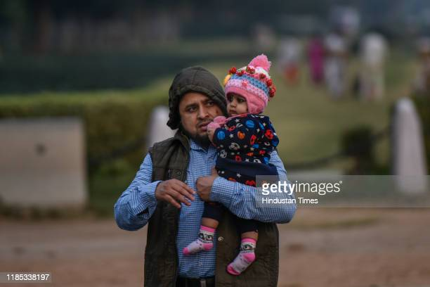 Man holds up his child as city witnessed cold waves throughout the day, which brought down the temperature, at Rajpath on November 28, 2019 in New...