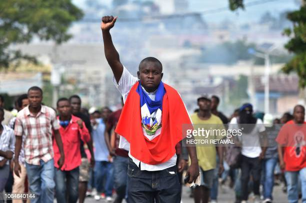 TOPSHOT A man holds up his fist as demonstrators march through the streets of PortauPrince on November 23 demanding the resignation of Haitian...
