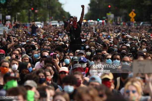 A man holds up his fist while hundreds of demonstrators march to protest against police brutality and the death of George Floyd on June 2 2020 in...