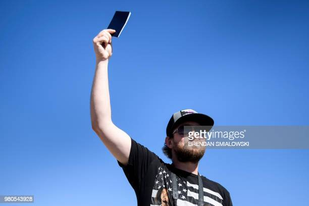 A man holds up his passport while mayors speak to the press outside at the Tornillo Port of Entry near El Paso Texas June 21 2018 during a protest...