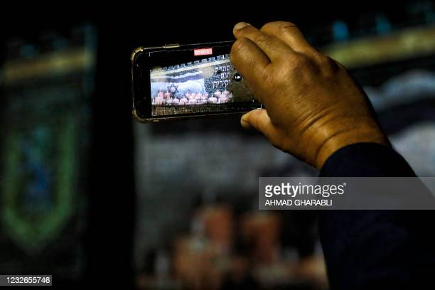 Man holds up his phone to film as a projection of an Israeli flag flying before lit candles is displayed on the old city walls of Jerusalem on May 2...