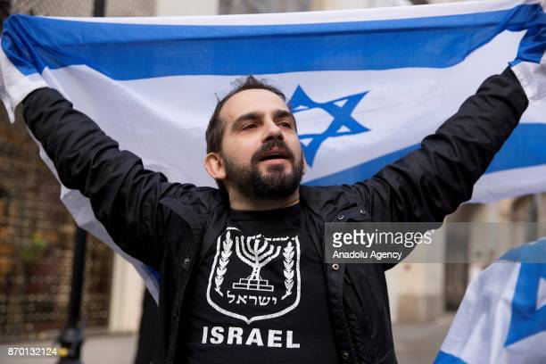 A man holds up Israeli flag as proPalestinian supporters hold a national march through central London England on November 4 demanding justice and...