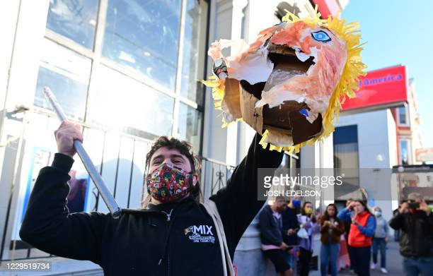 A man holds up the head of a Donald Trump pinata as people celebrate Joe Biden being elected President of the United States in the Castro district of...