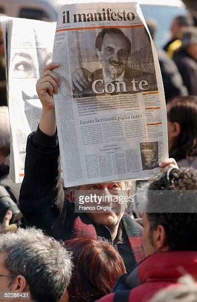 Man holds up the Italian journal Il Manifesto showing Italian intelligence officer Nicola Calipari on the front cover outside Santa Maria Degli...