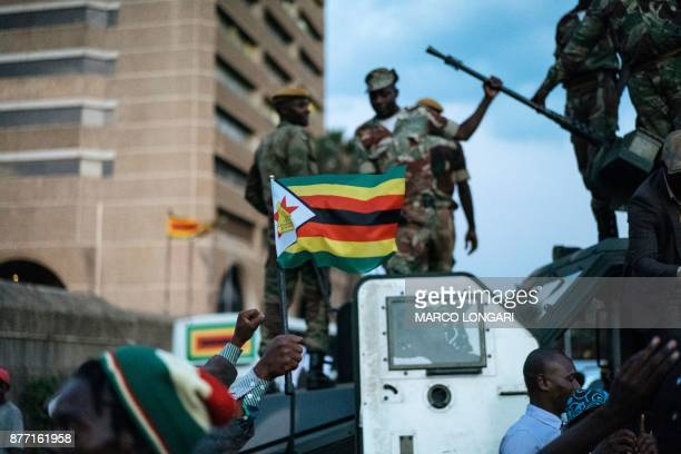 TOPSHOT A man holds up the national flag of Zimbabwe as Zimbabwean soldiers are celebrated by citizens in the streets in Harare on November 21 2017...