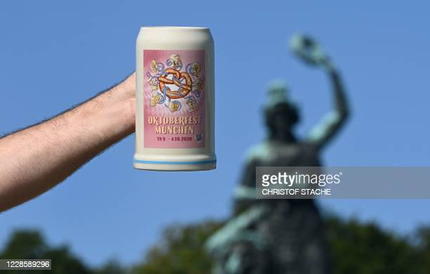 Man holds up the official 2020 Oktoberfest beer mug, in front of the Bavaria monument at Theresienwiese in Munich, southern Germany, the place of the...