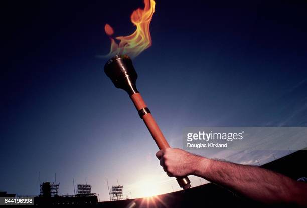 A man holds up the olympic torch at the Los Angeles Coliseum for the 1984 Summer Olympics
