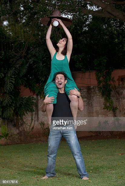 man holds up woman to change light bulb.  - nur erwachsene stock-fotos und bilder