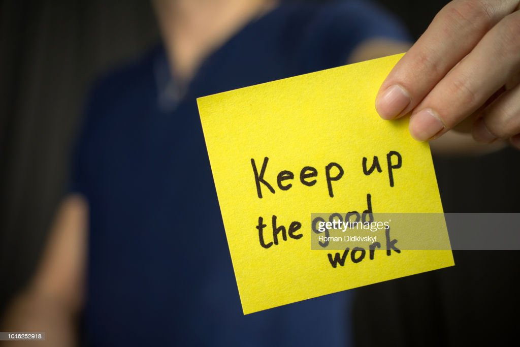 Man holds yellow sticker inscription Keep up the good work. : Stock Photo