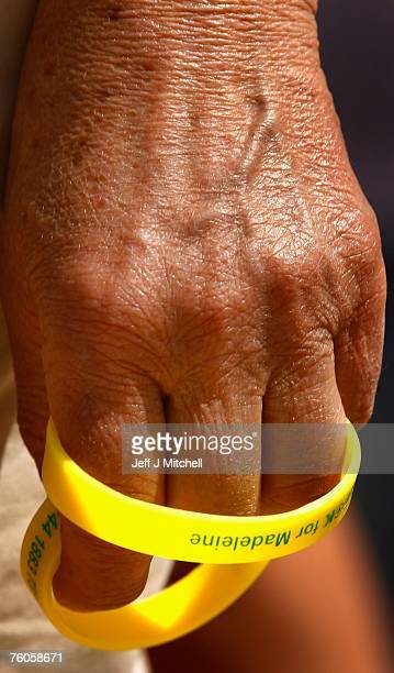 A man holds yellow wrist bands with Madeleine on them outside the church on August 11 2007 in Praia da Luz Portugal It has been 100 days since...