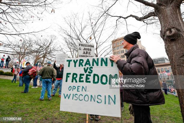 A man holsd sign during a protest against the coronavirus shutdown in front of State Capitol in Madison Wisconsin on April 24 2020 Gyms hair salons...