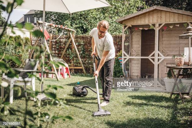 Man hoovering lawn in garden
