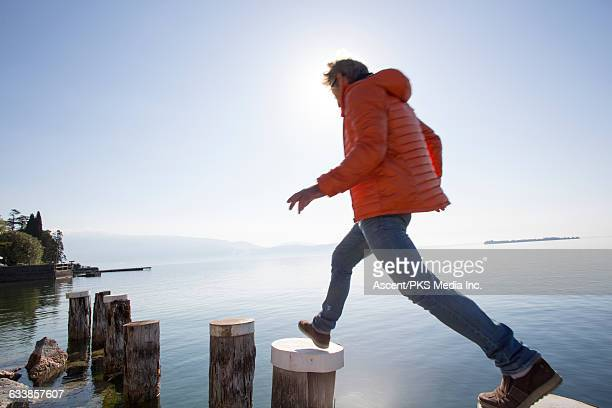 Man hops between dock posts above tranquil lake