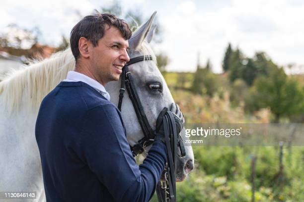 man horseback rider stroking white horse on its head - rein stock pictures, royalty-free photos & images