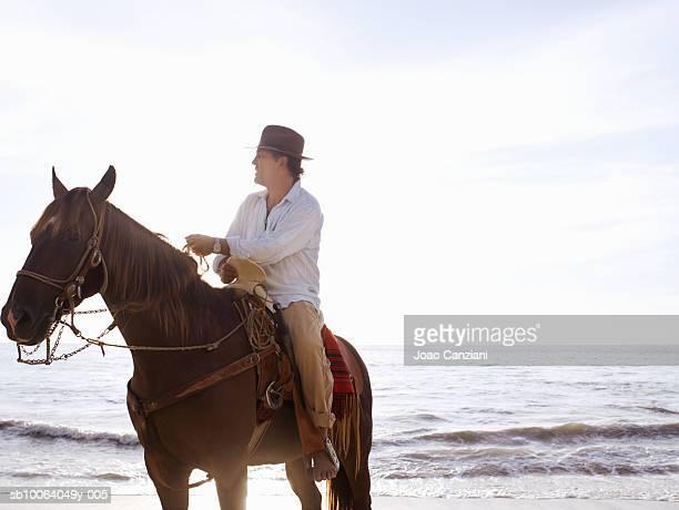 Man horseback riding on beach