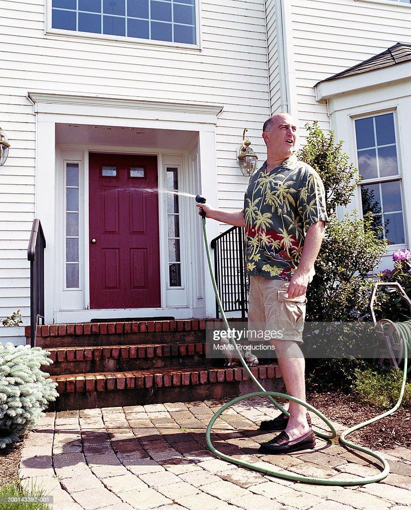 Man Hosing Down Front Door Looking Away Stock Photo