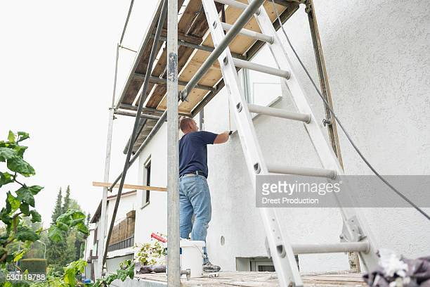 Man house scaffolding painting ladder working