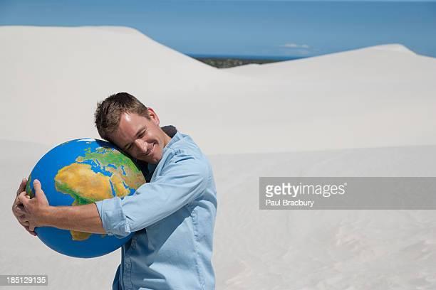 a man hugging a globe - world kindness day - fotografias e filmes do acervo