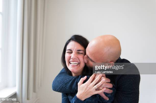 man hugging a woman - bald woman stock photos and pictures