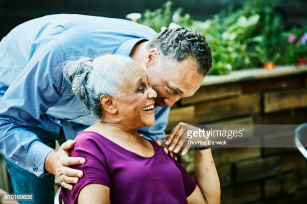 man hugging and kissing aunt before outdoor dinner party - aunt stock pictures, royalty-free photos & images