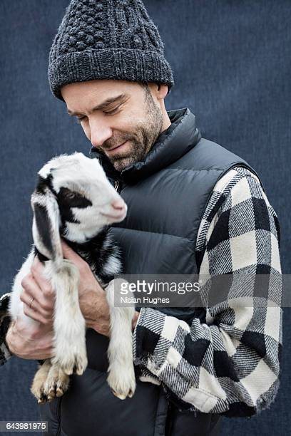 Man hugging baby goat and smilling