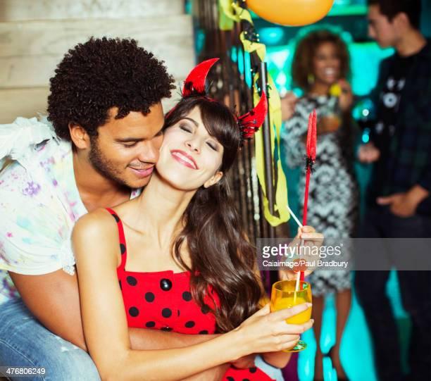 Man hugging girlfriend at party