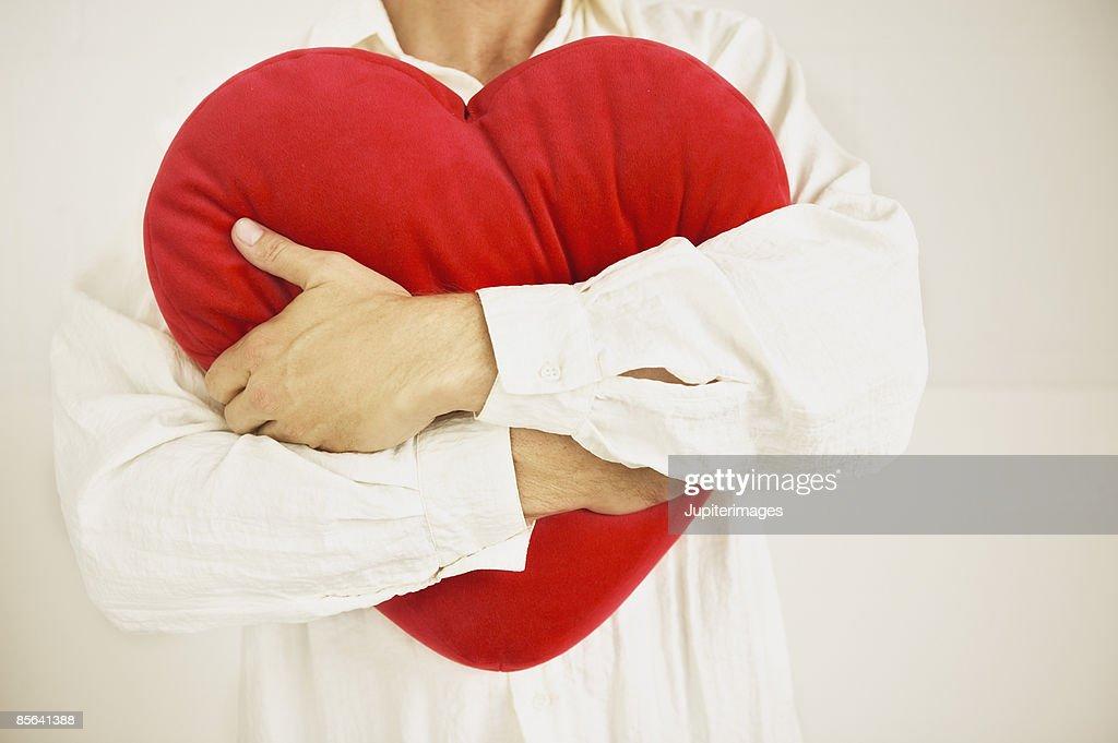 Man hugging heart-shaped pillow : Stock Photo