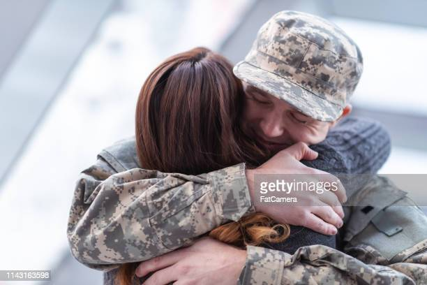 man hugging his wife after returning home from service - wife stock pictures, royalty-free photos & images