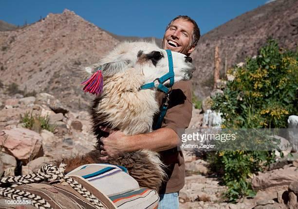 man hugging llama