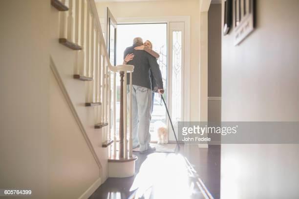 Man hugging visitor in front door