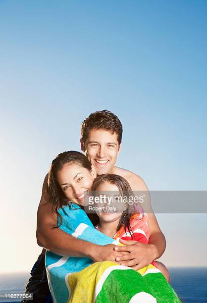 Man hugging wife and daughter wrapped in towel on beach