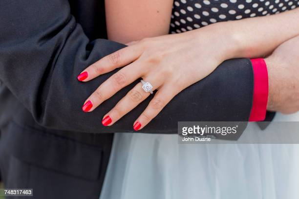 Man hugging woman wearing engagement ring on finger