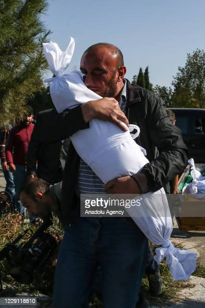 Man hugs a dead child draped in a white shroud during a funeral for those killed after ballistic missiles, allegedly launched by the Armenian army,...